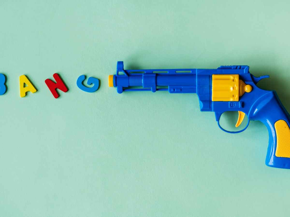 """Illustration: a plastic gun and letters that say """"bang"""""""