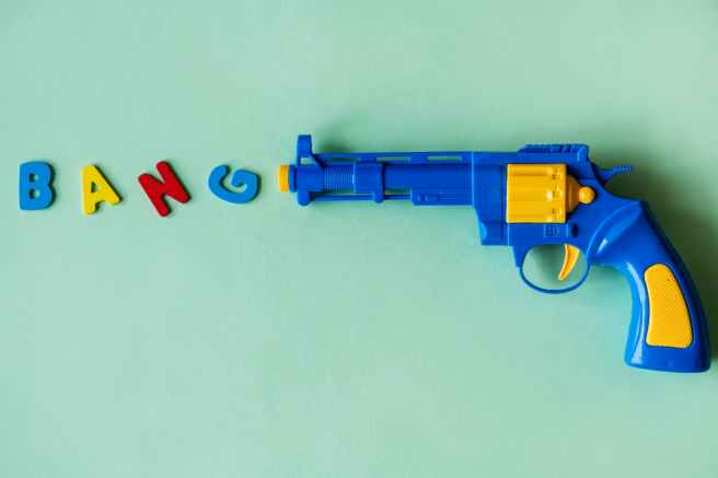 "Illustration: a plastic gun and letters that say ""bang"""